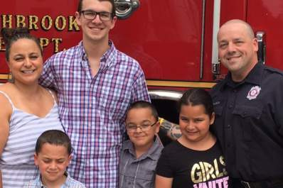 Firefighter Steve DeLuca and family pose in front of one of his station's trucks.