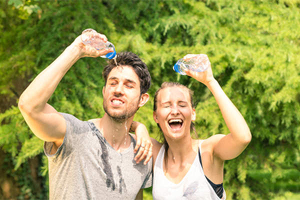 Sweaty couple pouring water on their head after exercise.