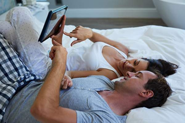 Couple lying in bed looking at a tablet.