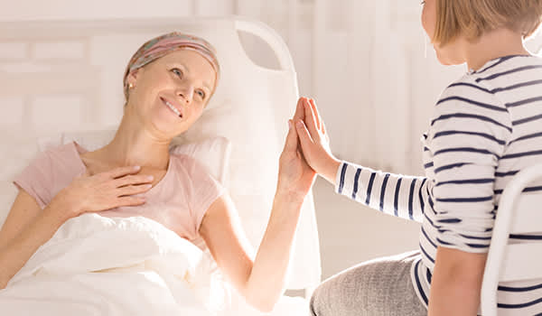 Mother with breast cancer smiling and touching her daughter's hand.