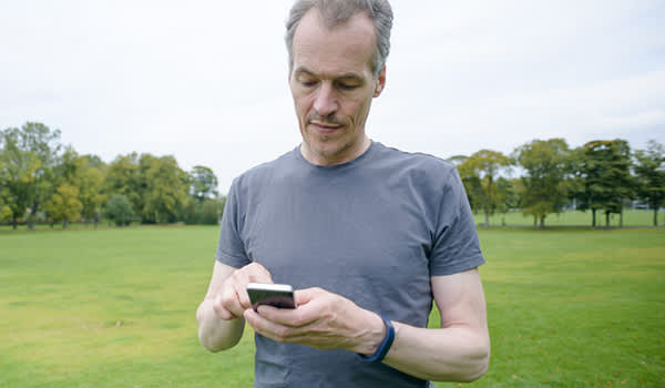 Middle aged male runner with smartphone app.