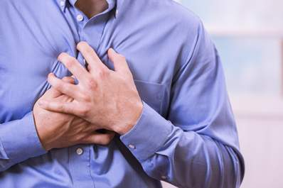Healthcare: Man clutching his chest in pain, possible heart attack