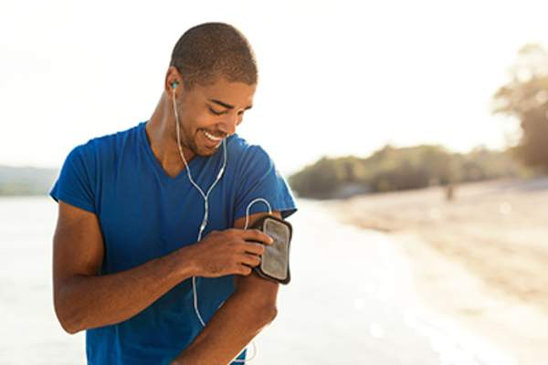 Healthy, smiling man listening to music out for a run.
