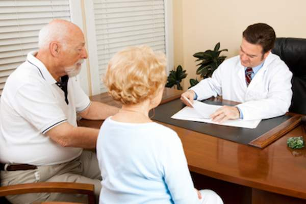 Doctor reviewing health records with older couple.