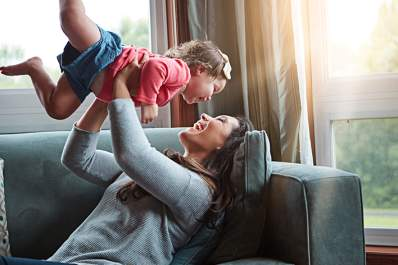 Mother playing with young daughter lifting her up and laughing.