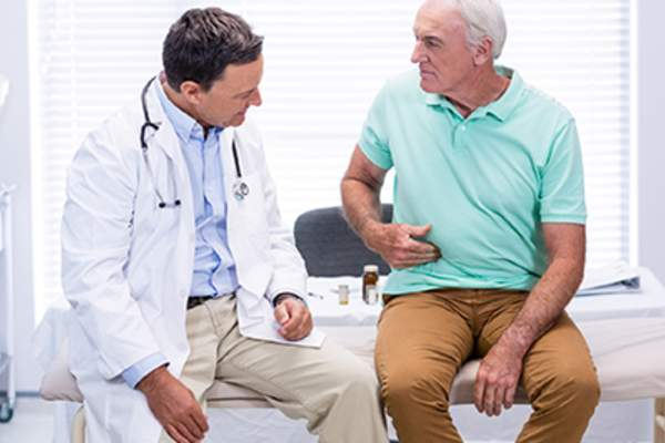Senior man showing stomach pain to doctor.