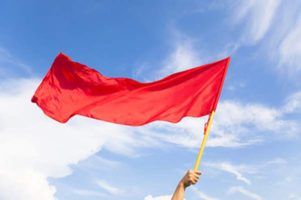 Holding red flag against blue sky.