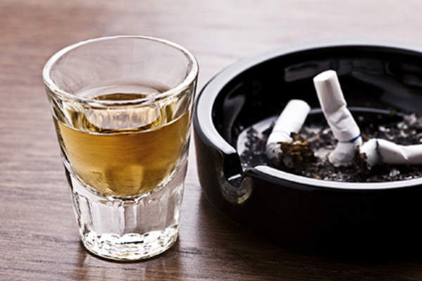Alcohol next to cigarettes in an ashtray.