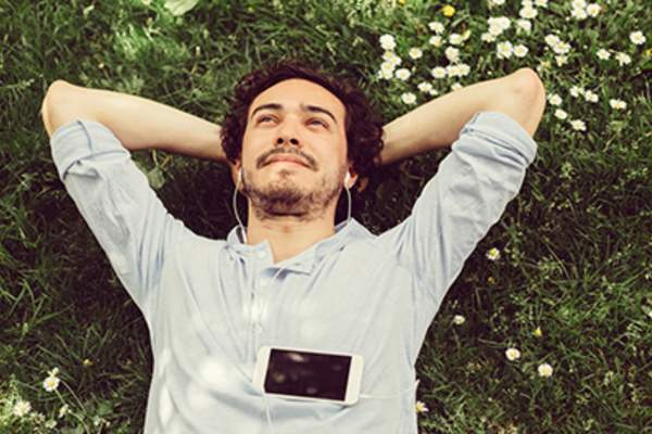 Man relaxing in the grass with phone
