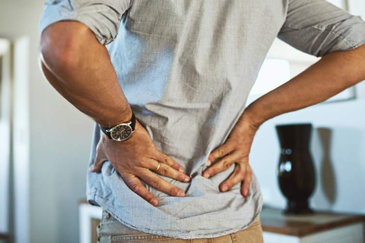 Man holding lower back in pain