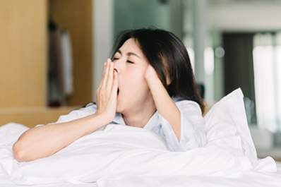 Woman yawning in bed.