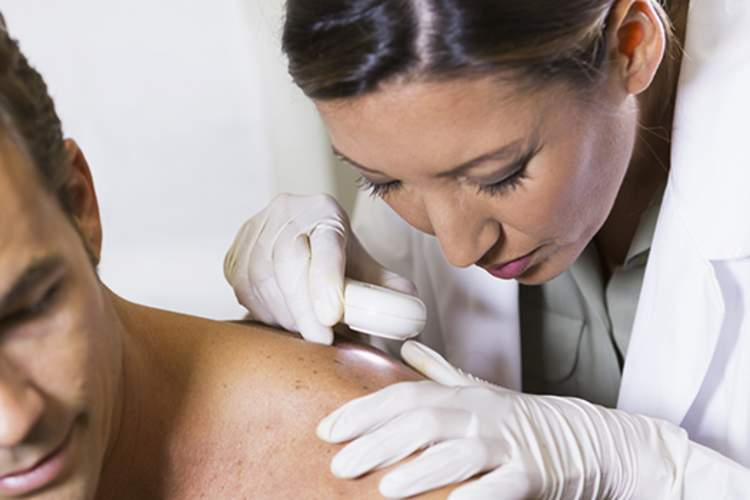Dermatologist checking skin on man's shoulder for skin cancer.