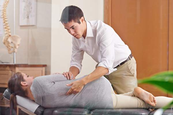 Osteopath adjusting female patient.