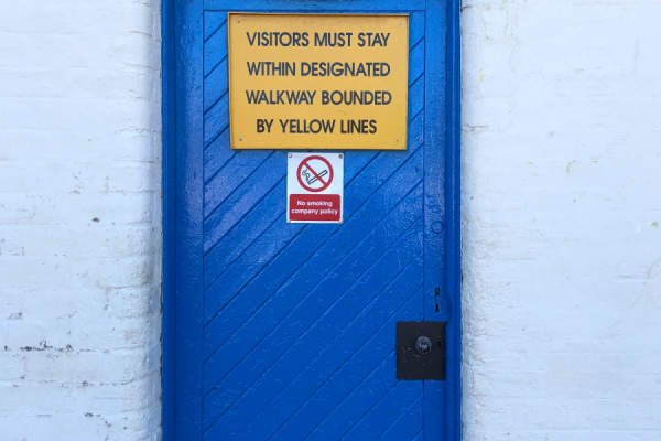 "blue door with sign reading ""Visitors must stay within designated walkway bounded by yellow lines"""