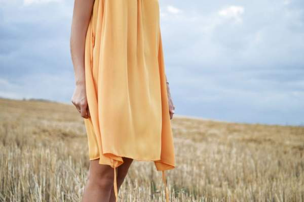 Woman wearing flowy yellow dress in field