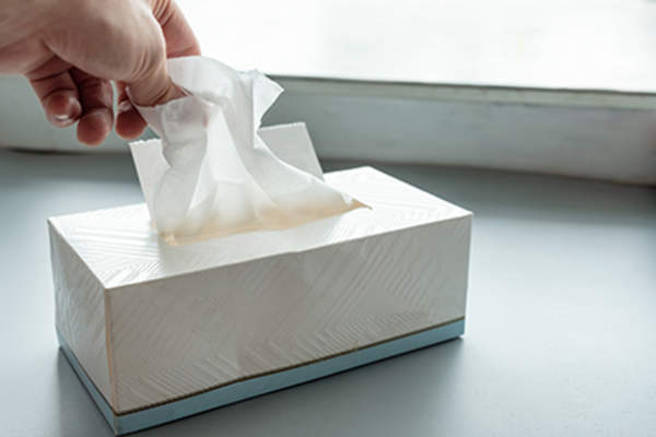Pulling a tissue out of a box.