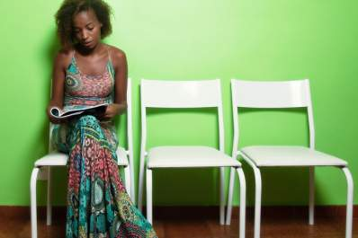 Young woman reading a magazine in a waiting room.