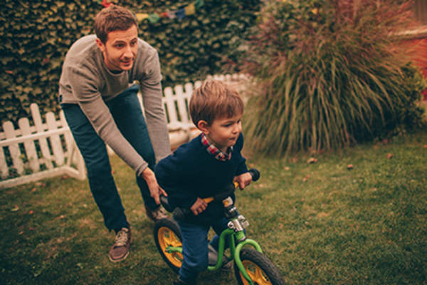 Father teaching his son how to ride a bike.