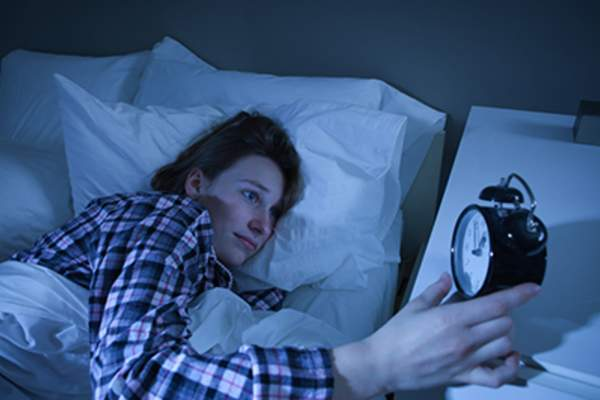 Woman with insomnia looking at alarm clock.