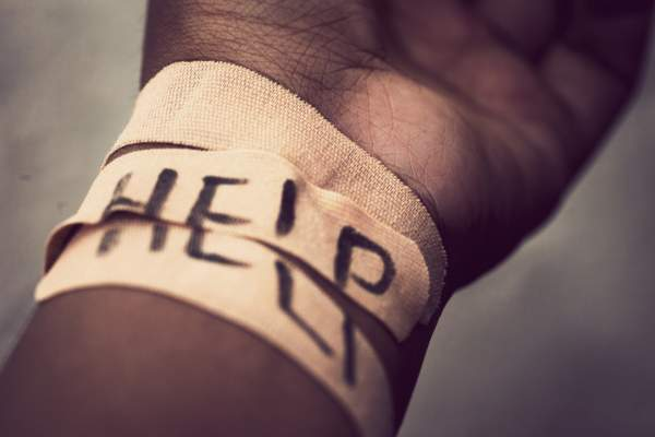 "Self-harm wrist covered with bandage, with ""HELP"" written across bandage."
