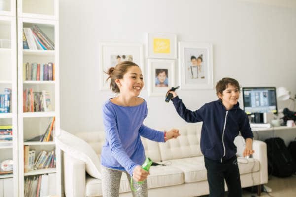 Kids dancing with video game controllers
