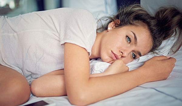 Young woman lying in bed worried.