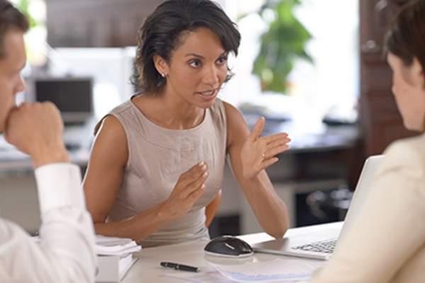 Woman gesturing while explaining something in a meeting.