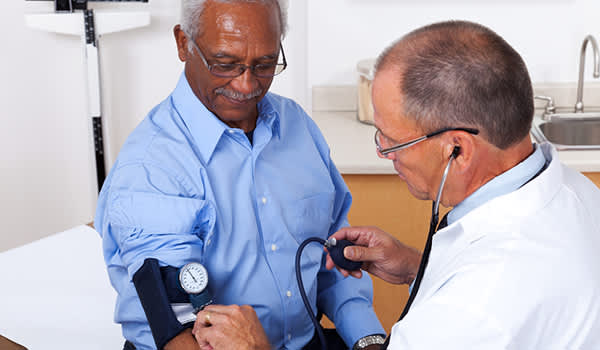 Doctor checking man's blood pressure.