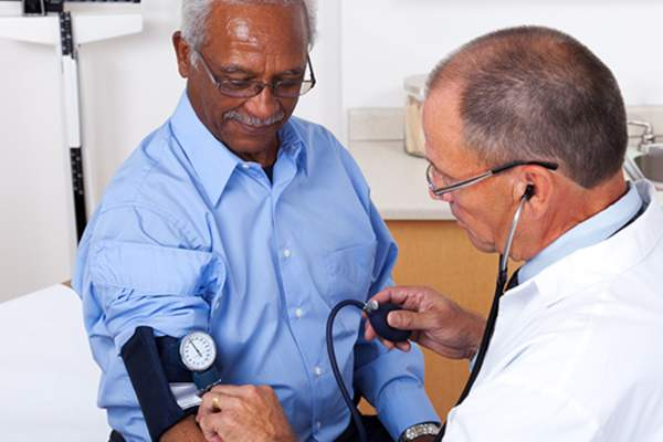 older man having blood pressure checked image