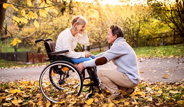 Senior man with wife in a wheelchair.