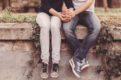 Couple holding hands while sitting on a wall.