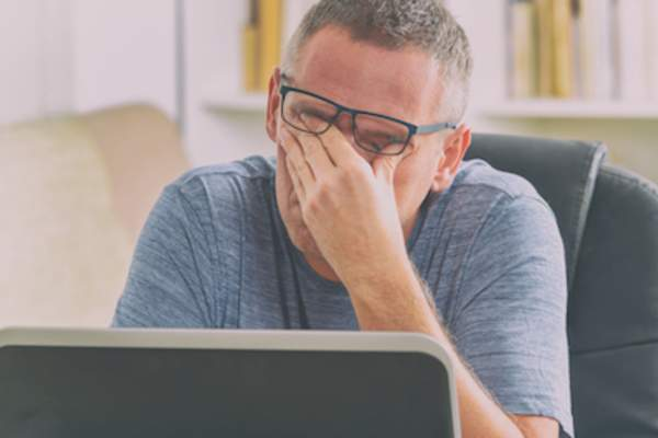 Stressed out man rubbing eyes while sitting at home computer.