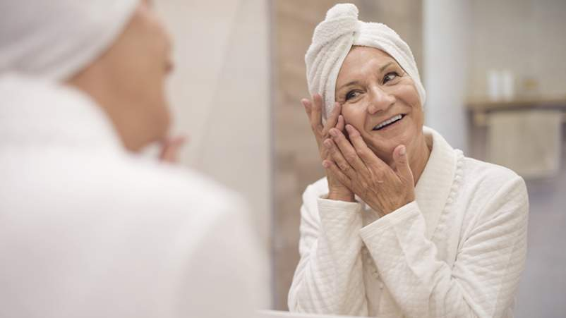 Senior woman applying moisturizer to her face to combat the symptoms of psoriasis.
