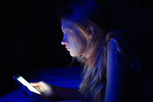 Teenage girl using cell phone at night.