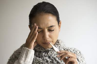 Woman with a fever checking her temperature.