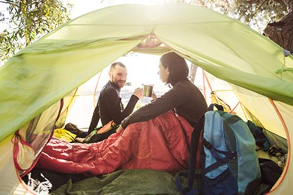 Couple drinking coffee while sitting in a tent.