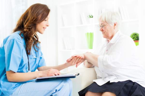 Nurse checking elderly lady's hand