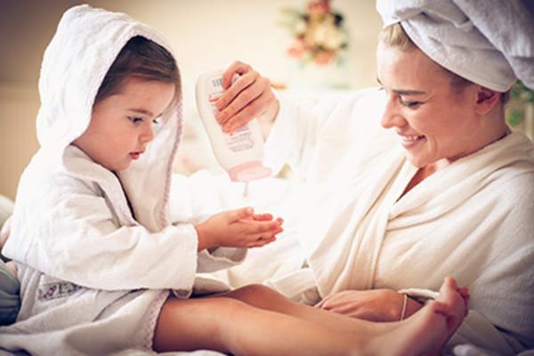 Mother helping her daughter put on lotion.
