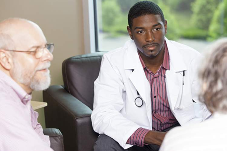 Older couple having serious discussion with doctor.