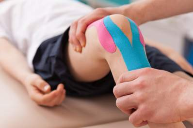 A man has kinesiology movement therapy for his knee.