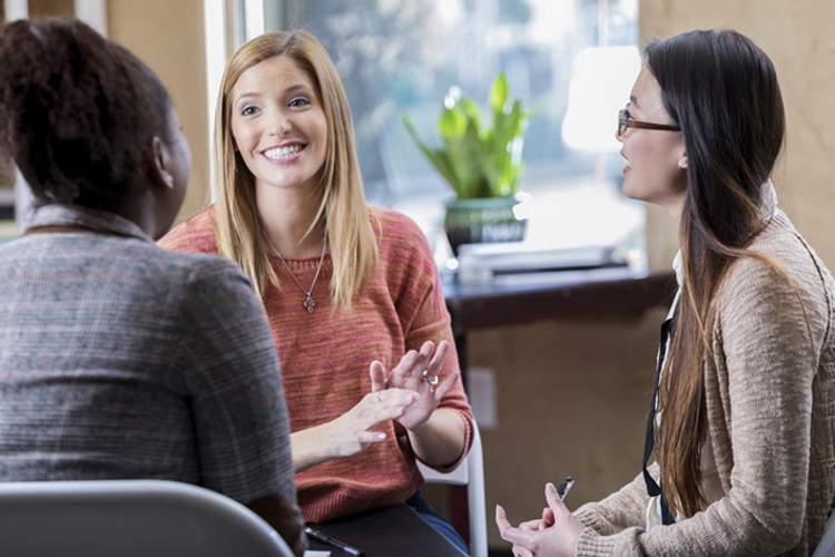 Happy young women talking in group therapy.