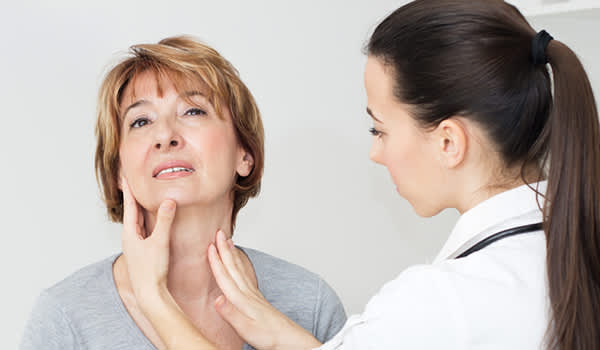 Doctor examining woman's thyroid gland.