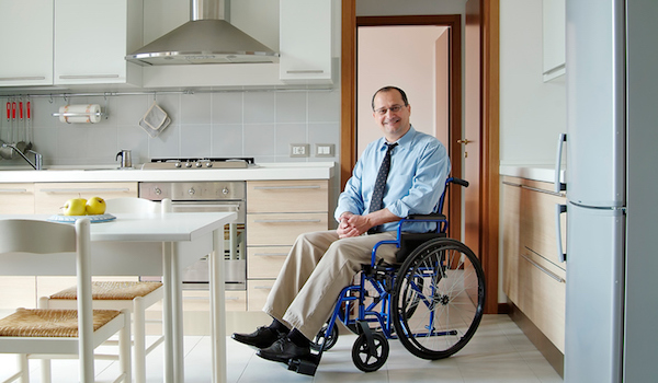 Man in wheelchair sitting in his accessible kitchen.