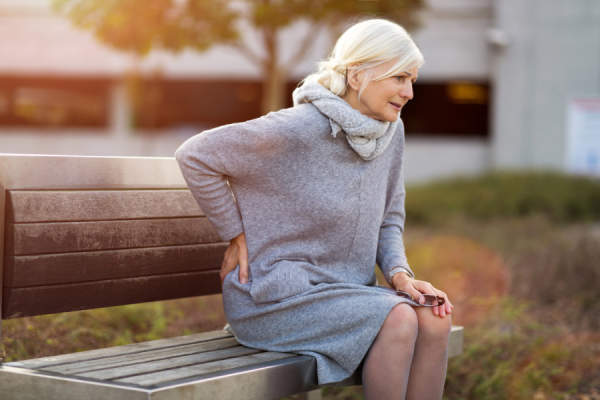 Senior Woman Suffering From Back Pain While Sitting On Bench
