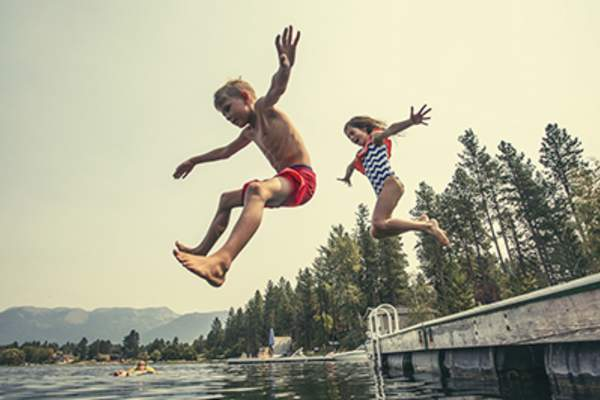 Kids jumping off the dock into a lake .