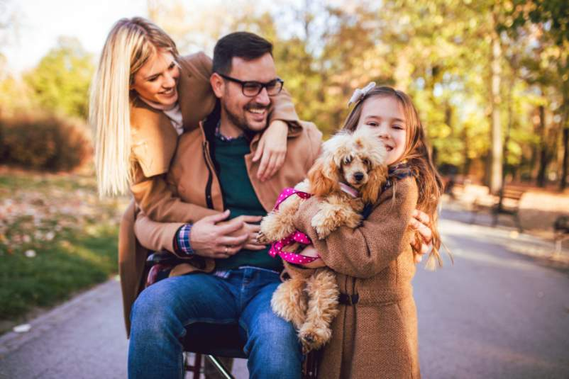 dad in wheelchair with wife and daughter and puppy