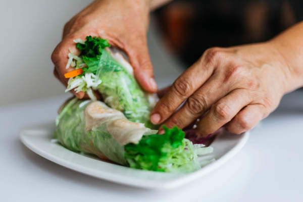 close up of hands picking up summer roll containing vegetables