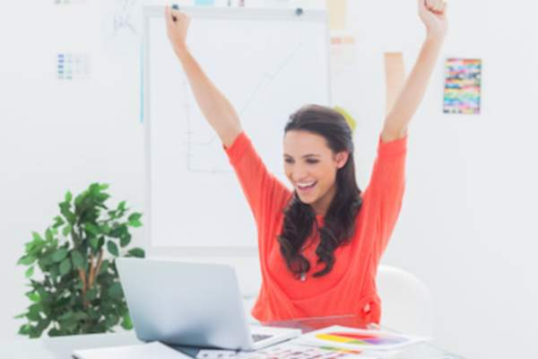 Woman at desk raising her arms in victory.