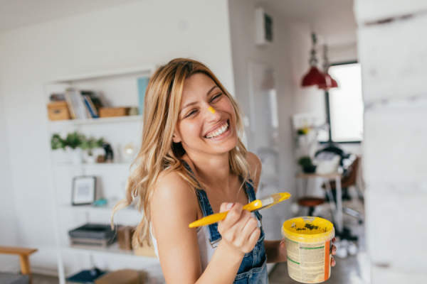 woman smiling holding paintbrush, yellow paint on nose