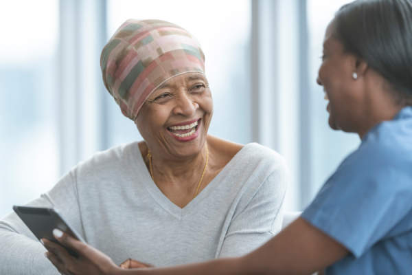 Senior woman with cancer smiling with doctor